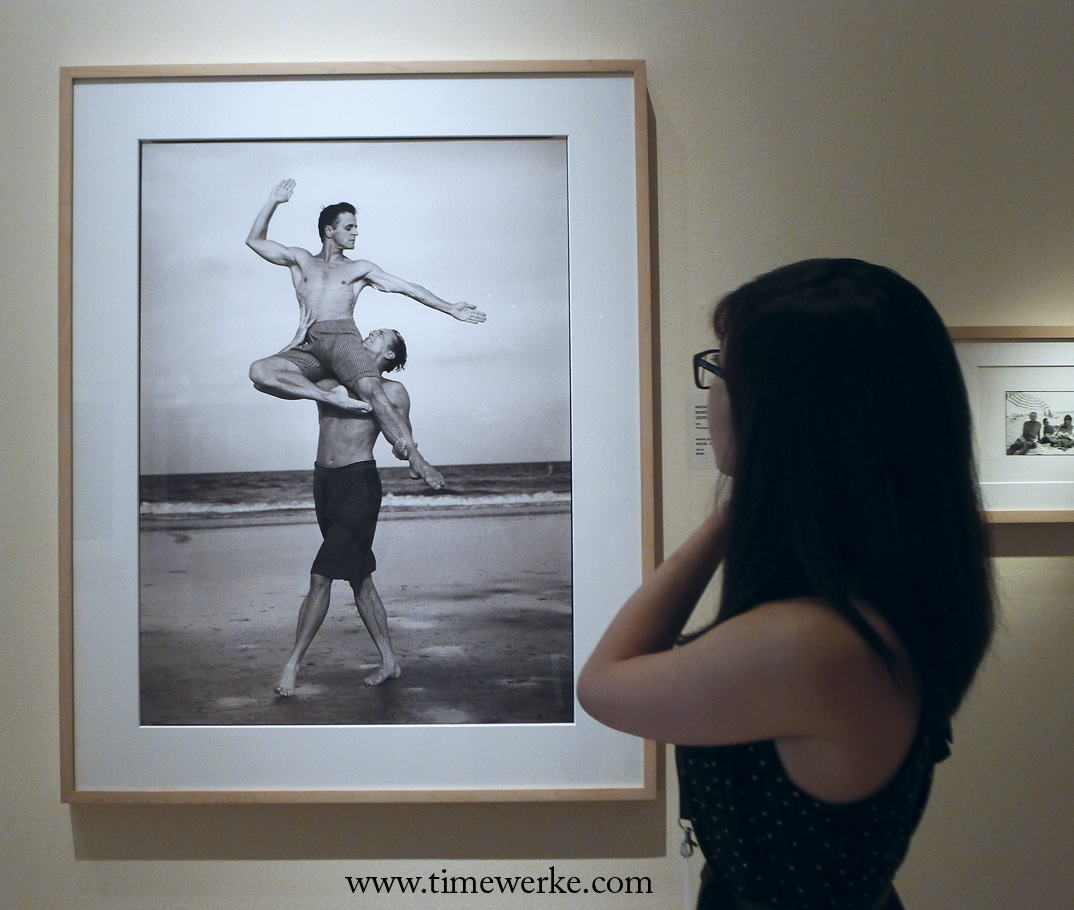 A young lady enjoying the photo of Mikhail Baryshnikov and Bob Besserer taken by Annie Liebovitz on Cumberland Island, Georgia in 1990. Photo: © TANG Portfolio