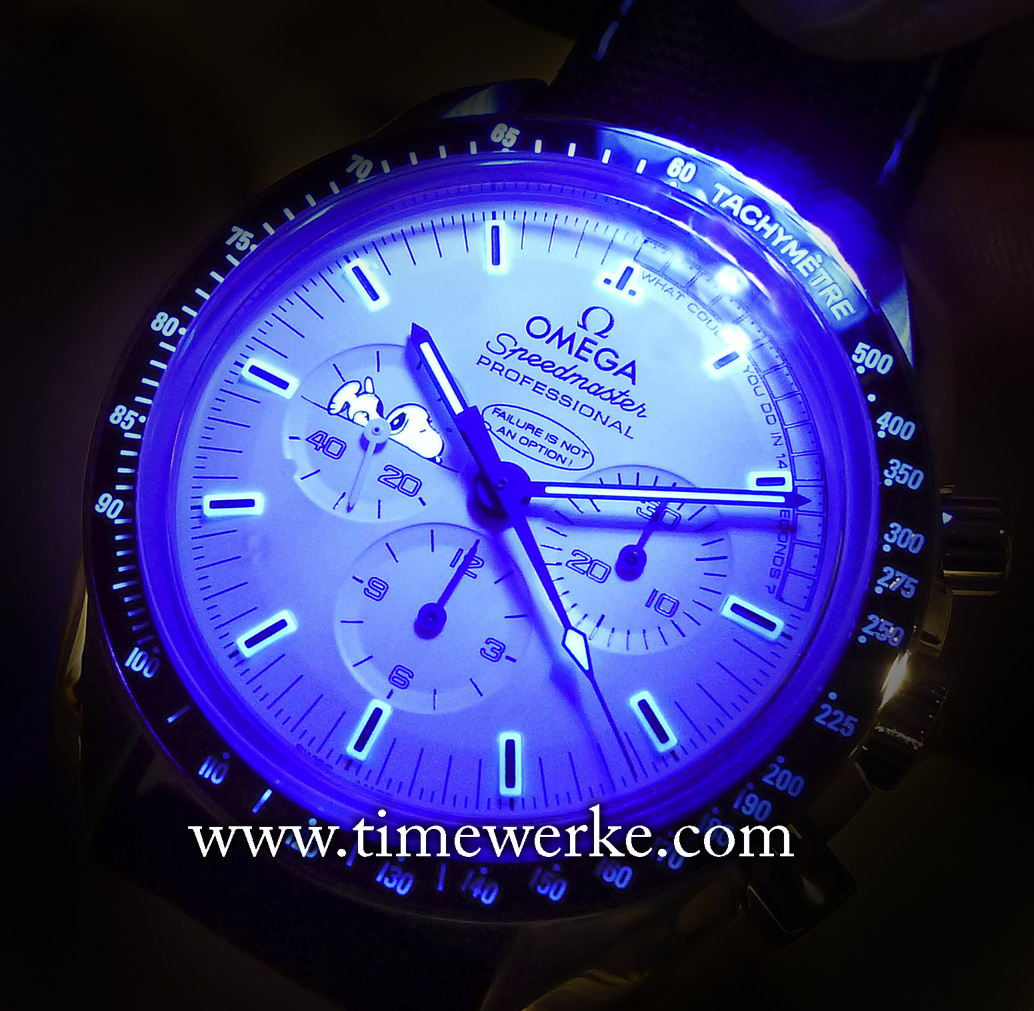 """Omega Speedmaster Apollo 13 Silver Snoopy Award. Using ultra-violet light to demonstrate the luminescence on the dial (this explains the """"blueness"""". Do note that the SuperLuminova is actually in green in darkness.) Not only are the hour, minute and seconds hands luminescent once """"charged"""", so are the hour markers including the sleeping Snoopy. This cute feature adds much character to the dial. Photo: © TANG Portfolio. Elfa / Timmy. BaselWorld 2015"""