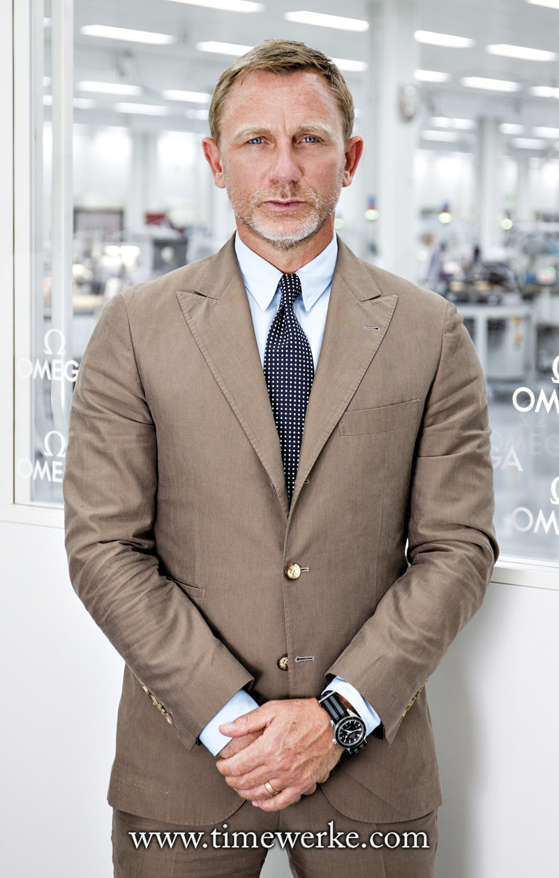 "British actor Daniel Craig who plays James Bond (his fourth starring role) in the 2015 movie Spectre. This photo was taken when Craig visited the Omega factory in Villeret, Switzerland. On his wrist: the Omega Seamaster 300 ""Spectre"" Limited Edition with the black and grey NATO strap. Craig wore the Seamaster 300 ""Spectre"" in the movie as well. Is the James Bond black and grey NATO strap with five stripes a myth? Or is it a reality? Photo: © Omega"